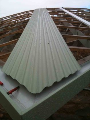 The barn roof with a slight hip break so the first piece of tin goes on this to make sure it is rapted nicely.